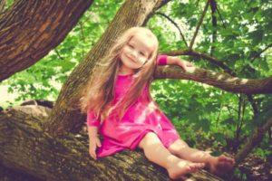 Счастливая девочка сидит на дереве