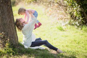 Счастливая мама держит на руках ребенка в парке