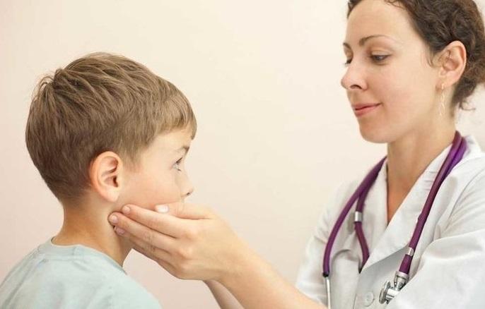 Врач осматривает лимфоузлы на шее у ребенка