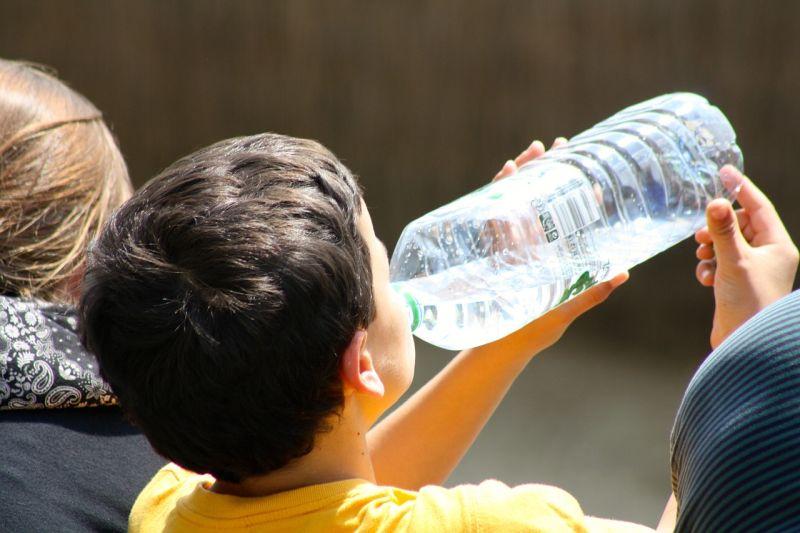 Ребенок пьет воду из бутылки