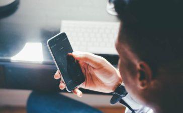 Подросток держит в руке телефон