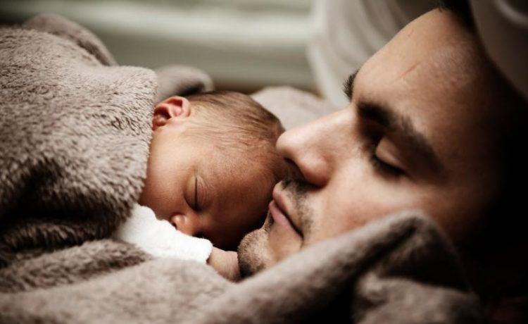 Младенец спит рядом с отцом
