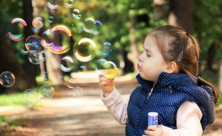 Маленькая девочка пускает пузыри на улице